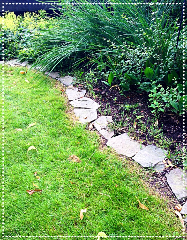 Stone is used as edging around this flower border