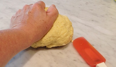 Photo of kneading dough on a marble surface.